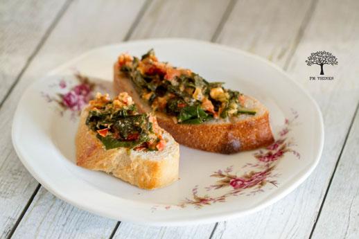Mangold-Feta-Creme auf frischem Baguettebrot und Ciabattabrot auf Teller auf Holztisch