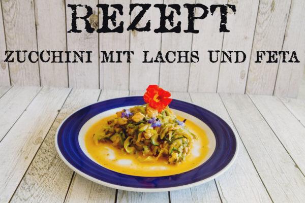 Zucchini mit Lachs und Feta auf Teller auf Holztisch