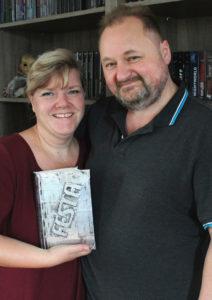 Inge und Frank Festa vom Festa Verlag vor Bücherregal mit Buch mit dem Festa Logo in der Hand - Interview mit dem Festa Verlag